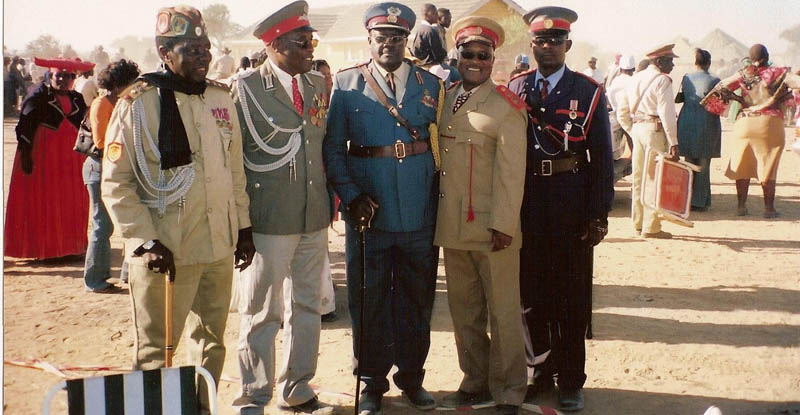 L-R: Jimmy Katuuo (Germany), Luther Zaire (Germany), Paramount Chief Kuaima Riruako, Dr. Ngondi A. Kamatuka (U.S.A.), last person unidentified. Picture taken at the Ovaherero Genocide Remembrance, August 14, 2004, Okakarara, Namibia.